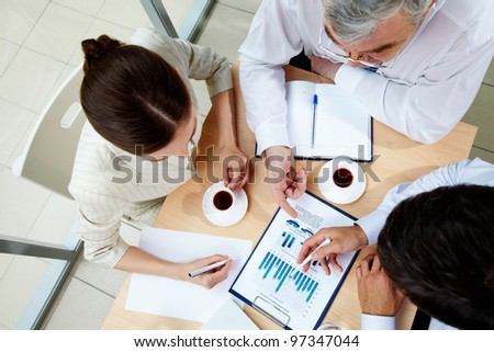 Above angle of business team discussing business documents at meeting