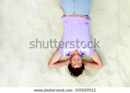 Above angle of handsome teenager lying on sand and laughing