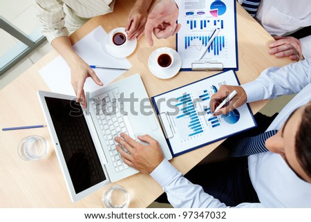 Above angle of human hands with business documents and laptop at meeting