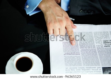 Above angle of male hand pointing at article in newspaper with cup of coffee near by