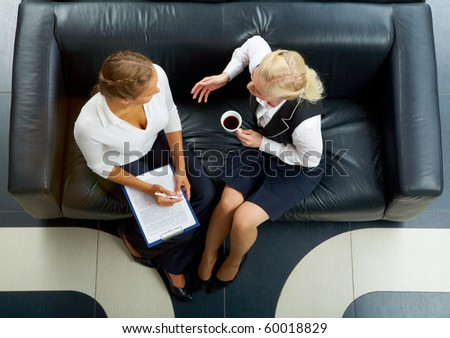 Above angle of two friendly employees sitting on sofa and planning work