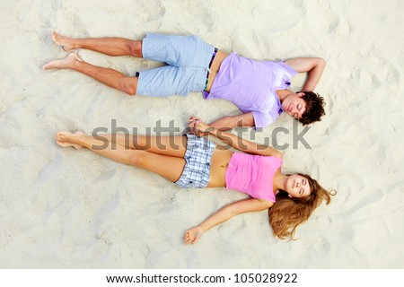 Above angle of two teenage friends lying on sandy beach and holding by hands