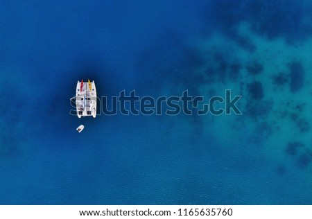 Above drone shot of a sailing catamaran at anchor in beautiful clear blue water. #1165635760
