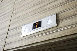 Above elevator door digital display with number seven floor.