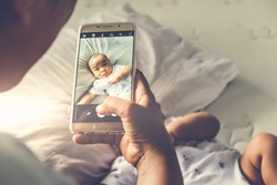 Above high angle shot of happy mom taking photo her Asian baby boy in bed with a smartphone at home. It is a memorable authentic feeling for every parent when their child is growing up. Top down view