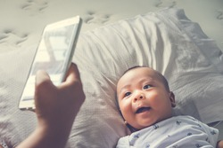 Above high angle shot of happy mom taking photo her Asian baby boy in bed with a smartphone at home. It is a memorable feeling for every parent when their child is growing up. Top down. Overhead view