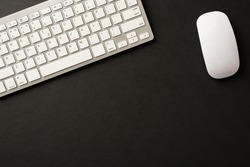 Above overhead view photo of wireless keyboard and mouse in white color isolated black backdrop with blank space
