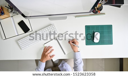 Above shot, Man writing notebook on modern office workspace table. #1523623358