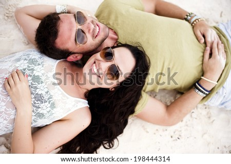 Above shot of a young couple in love in a tropical beach. Shot from above.