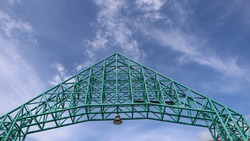 Above the entrance arch is made of steel frame and bright sky.