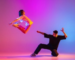 Above the ground. Two young people, guy and girl, dancing contemporary dance over pink background in neon light. Modern dance aesthetics concept