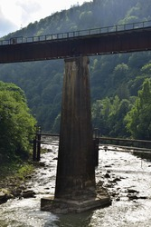 Above the turbulent mountain river, a pedestrian bridge with railings rises on long concrete columns. Photographed in the summer, no people