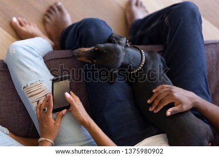 Photo of Above top cropped image black couple sitting on couch use phone surfing internet social networks having fun on lazy weekend family spends free time with domestic pet leisure activities at home concept