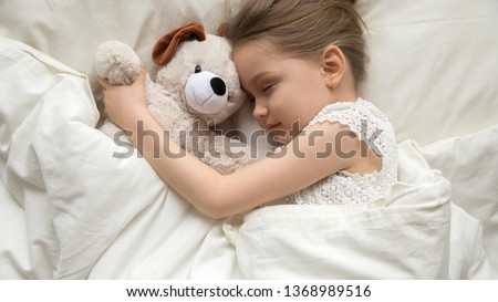 Above top view adorable slumber little girl embrace stuffed toy dog sleeping in comfortable bed with white fresh linens, closed eyes kid resting having daytime nap refreshment, bedtime ritual concept