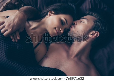Above top view close up cropped photo of lovely graceful tender cute smiling beautiful sexualcouple, they are hugging under blanket in bed on dark bedsheet, man is kissing gently his woman in forehead