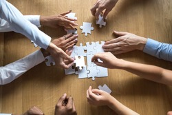 Above top view to the hands of diverse people assembling connecting jigsaw puzzle associates put pieces searching common solutions making right decisions together. Support and help in business concept