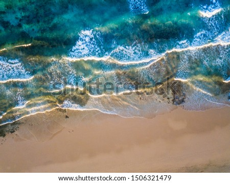 Above vertical view of blue ocean waves and yellow sandy beach - summer holiday vacation concept - travel and scenic place - energy nature outdoors with nobody there #1506321479