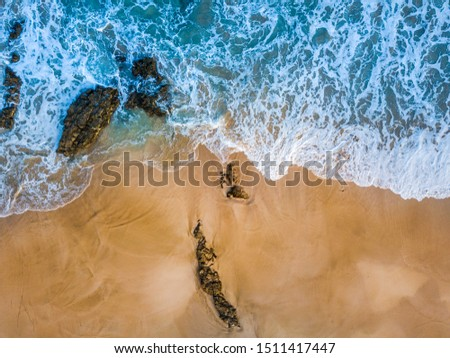 Above vertical view of blue ocean waves and yellow sandy beach - summer holiday vacation concept - travel and scenic place - energy nature outdoors with nobody there