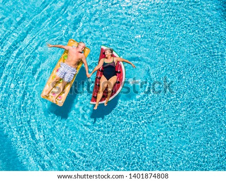 Above vertical view of people old senior couple taking hands with love and having fun on the blue clear swimming pool together enjoying the summer holiday vacation with trendy coloured lilos mattress