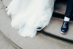 Above view at the newlywed legs on the staircases. Look of the kong wedding dress of the bride and groom shoes.