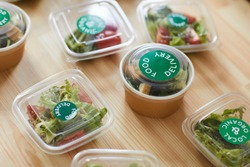Above view background of healthy food portions in plastic packaging on wooden table in food delivery service, copy space
