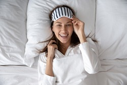Above view beautiful woman wear white nightwear, uses striped eye mask accessory for comfortable nap, lying in bed awakened in early morning feels rested and fresh getting enough quality sleep concept
