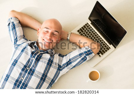 Above view of a businessman resting on the floor with smile after exhausted working day
