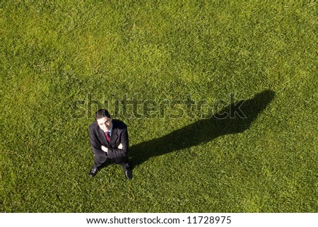 Above view of a businessman standing on the grass (with copy space) - stock photo