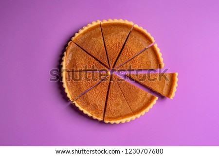 Above view of a pumpkin pie cut in slices with one piece separated, on a purple background. Minimalist food image. Thanksgiving traditional dessert. #1230707680