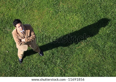 Above view of a serious business man with his shadow on the grass