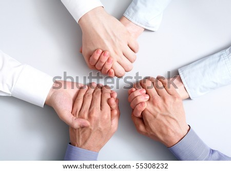 Above view of business partners hands holding each other symbolizing support