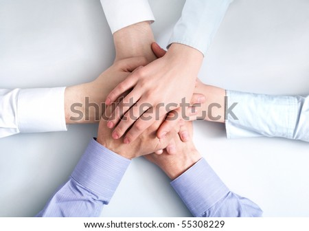Above view of business partners hands on top of each other symbolizing companionship and unity