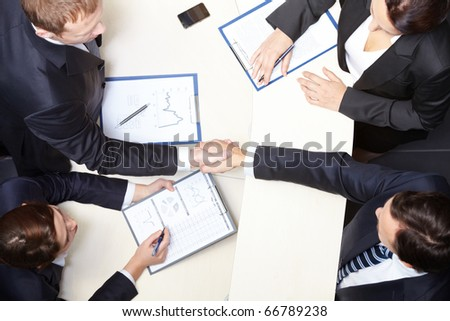 Above view of business partners handshaking after signing contract