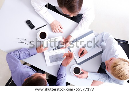 Above view of business people working with documents at meeting