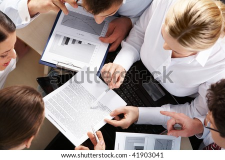 Above view of business team looking at paper during meeting and discussing it