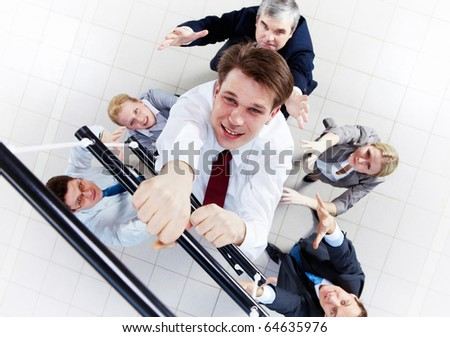 Above view of businessman ascending the ladder with his crew beneath