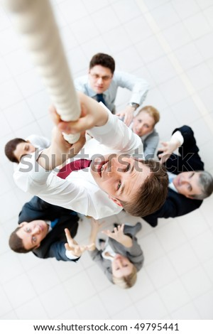 Above view of businessman ascending up the rope with his crew beneath