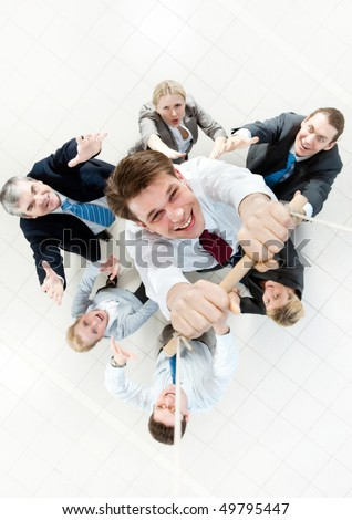 Above view of businessman holding plank on ropes and hanging on it with supporting crew beneath
