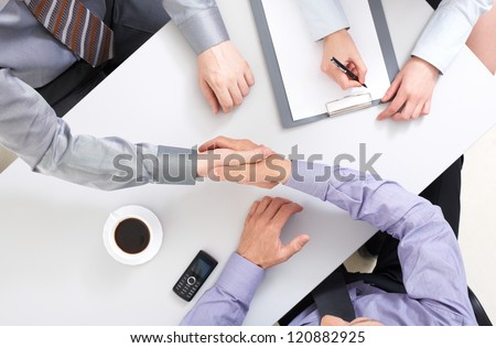 Above view of businessmen doing agreement at workplace