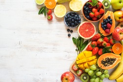 Above view of colorful fruits, strawberries, blueberries, mango, orange, grapefruit, banana, apple, grapes, kiwis on the white background, copy space for text, selective focus