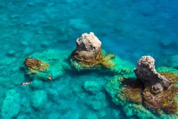 Above view of couple snorkeling in turquoise sea water, Glyka Nera, Chania, Crete, Greece