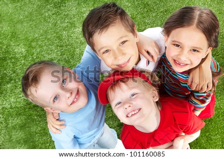 Above view of cute children hugging and smiling at cam