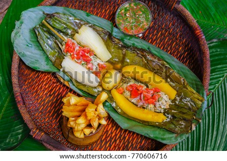 Shutterstock Above view of delicious typical amazonian food, fish cooked in a leaf with yucca and plantain, bowl of salad and fried yucca, served in a wooden plate over a wooden table