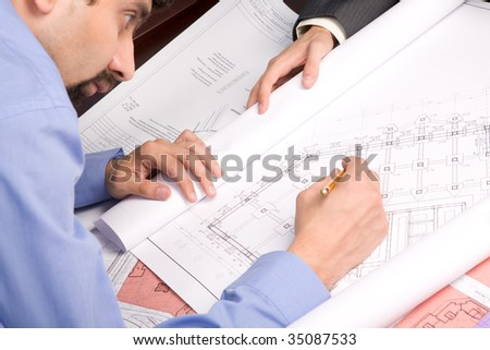 Above view of engineer over blueprint while working at new draft
