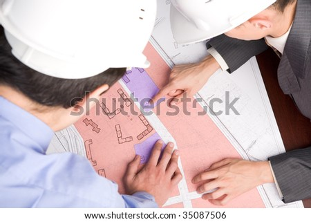 Above view of engineers looking at blueprints with sketches of projects