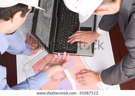 Above view of engineers looking at blueprints with sketches of projects while one of them typing on laptop keyboard