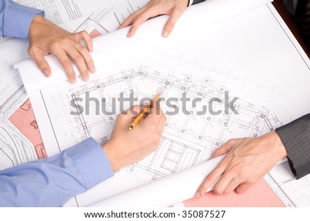 Above view of engineers over blueprints during work planning