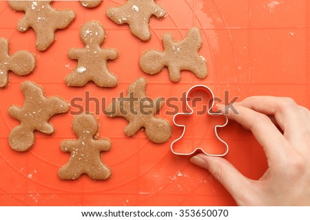Above view of female hand with cutter making sweet homemade Christmas cookies. Sweet dough for traditional gingerbread man cookies