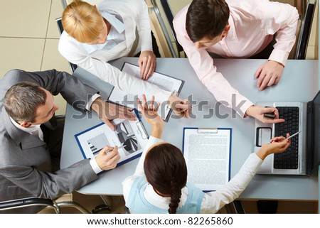Above view of four business partners interacting at meeting