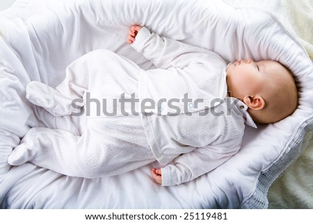 Above view of fragile baby having a nod in comfortable cradle at home